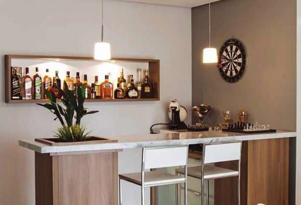 O nicho de madeira na parede acomoda diversas garrafas no ambiente