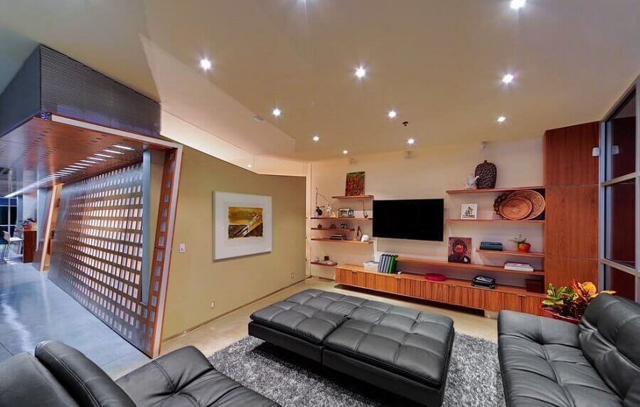 O rack de madeira combinou com o sofá de couro preto
