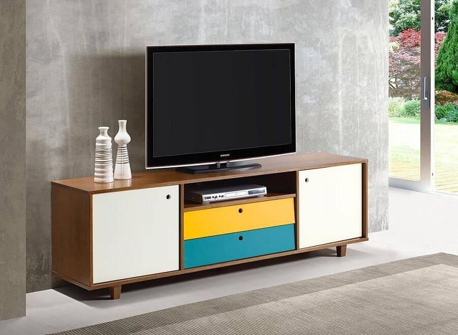 Os detalhes coloridos do rack de madeira deixam o móvel mais divertido