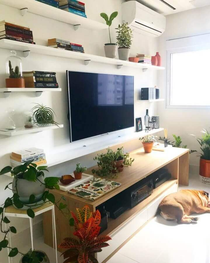 Parede branca e rack de madeira para a sala de estar