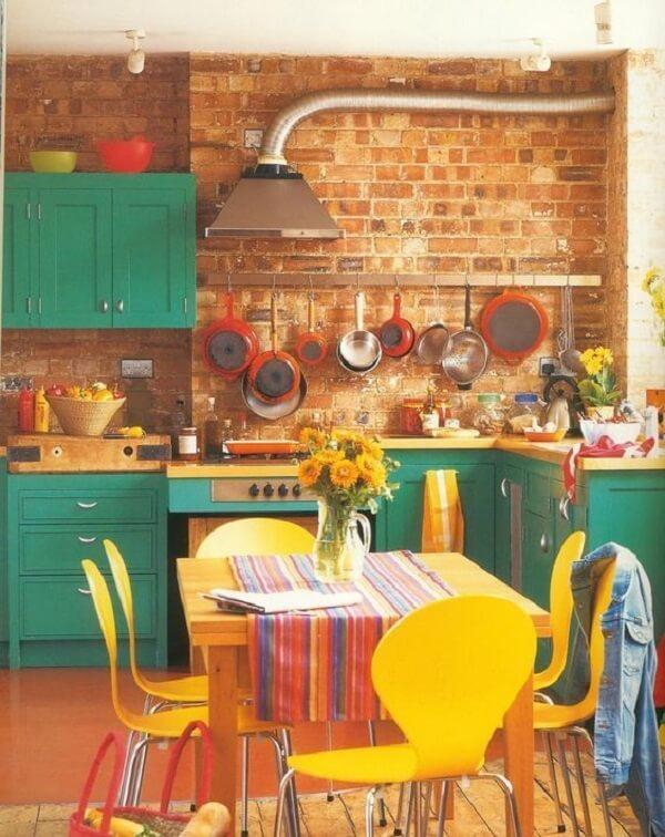 Parede de tijolinhos e cadeiras para cozinha coloridas trazem descontração para o espaço