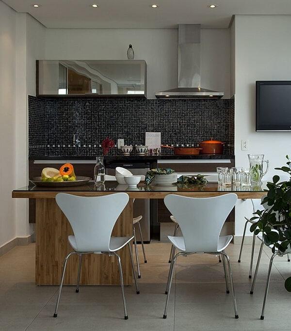 Parede revestida com pastilhas pretas e cadeiras para cozinha brancas decoram o ambiente
