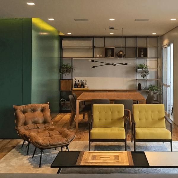 Poltrona costela marrom delimita o espaço da sala de estar