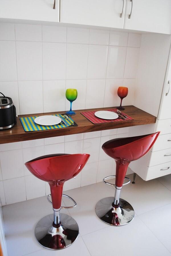 Projeto com pisos para cozinha branco e banquetas vermelhas. Projeto por Bianchi & Lima Arquitetura