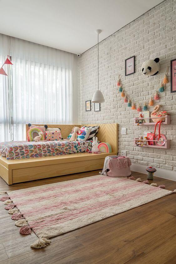 Quarto com cama infantil de madeira e tapete listrado rosa