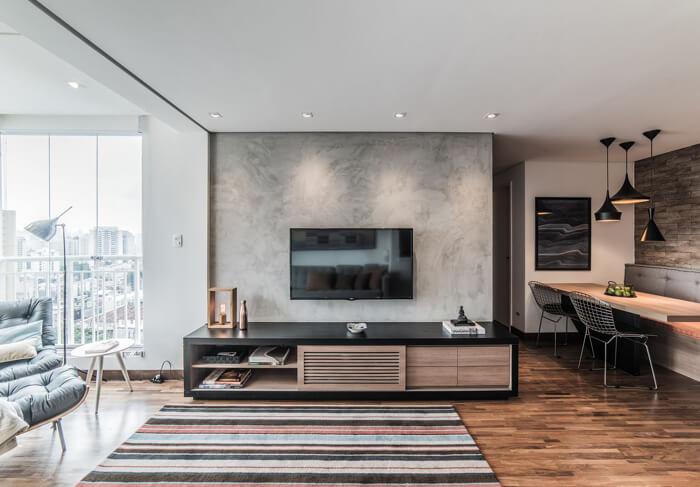 Sala com parede de cimento queimado e rack preto