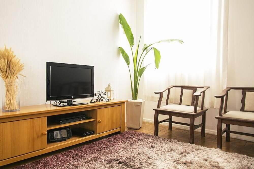 Sala de estar aconchegante com rack de madeira