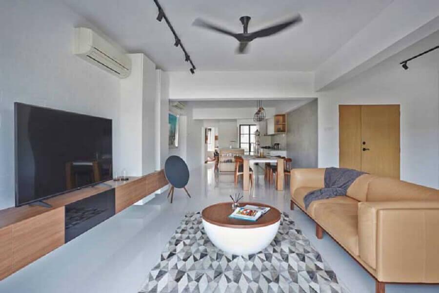 Sala de estar ampla decorada com sofá de couro e rack de madeira moderno
