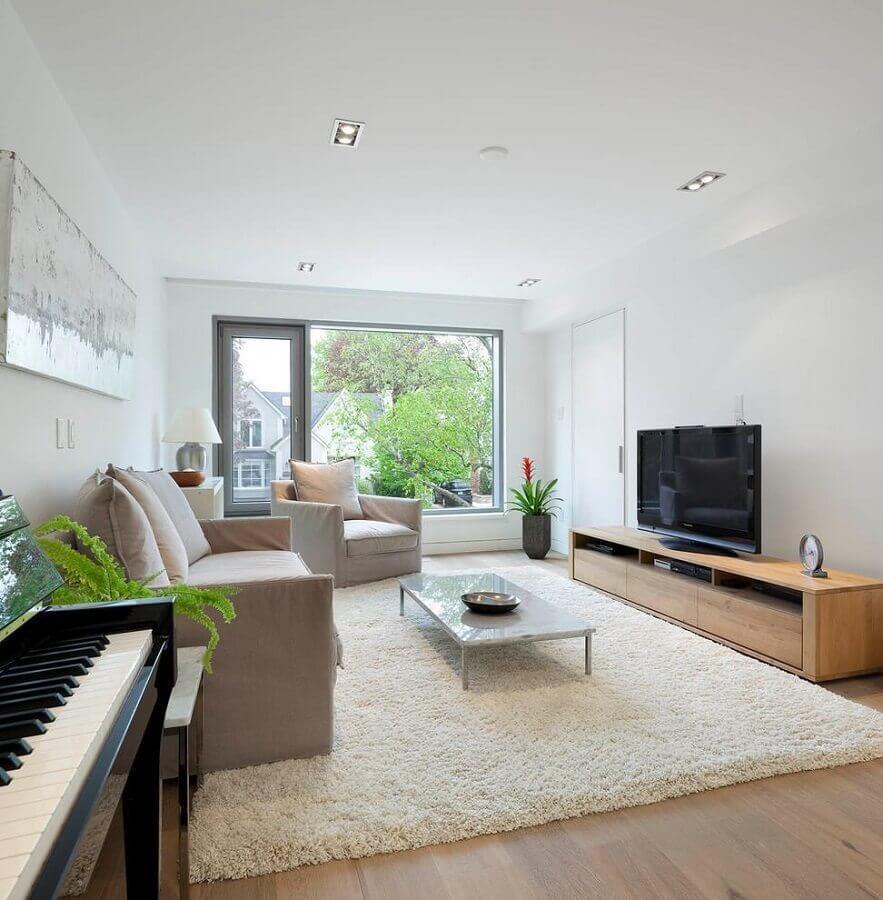 Sala de estar ampla decorada com tapete felpudo e rack de madeira