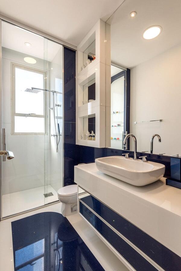 Silestone azul traz um toque diferenciado para esse banheiro com box de vidro. Fonte: Iara Kílaris