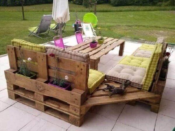 Sofá de palete em l na área externa com almofadas confortáveis