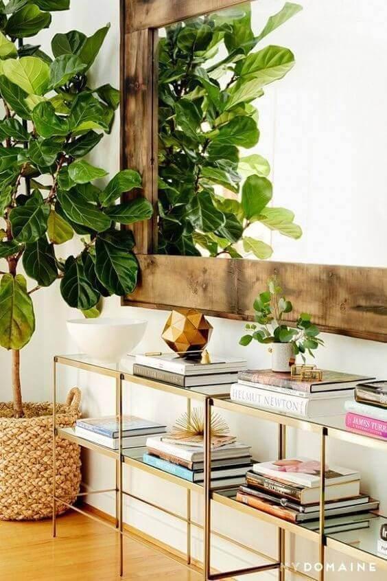 Aparador para sala dourado com livros decorando o ambiente