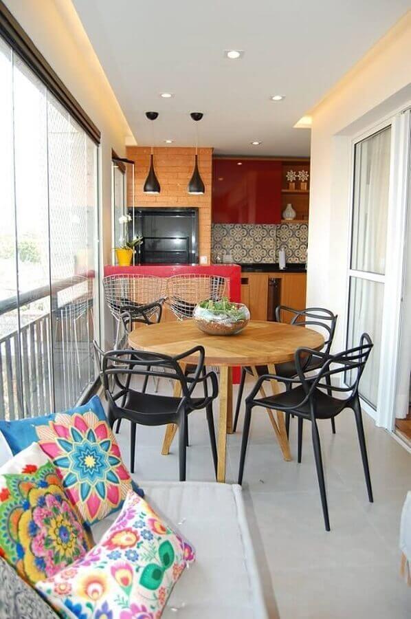 apartamento com área gourmet pequena e simples decorada com mesa de madeira redonda e bancada vermelha Foto Big Interior Design Blog