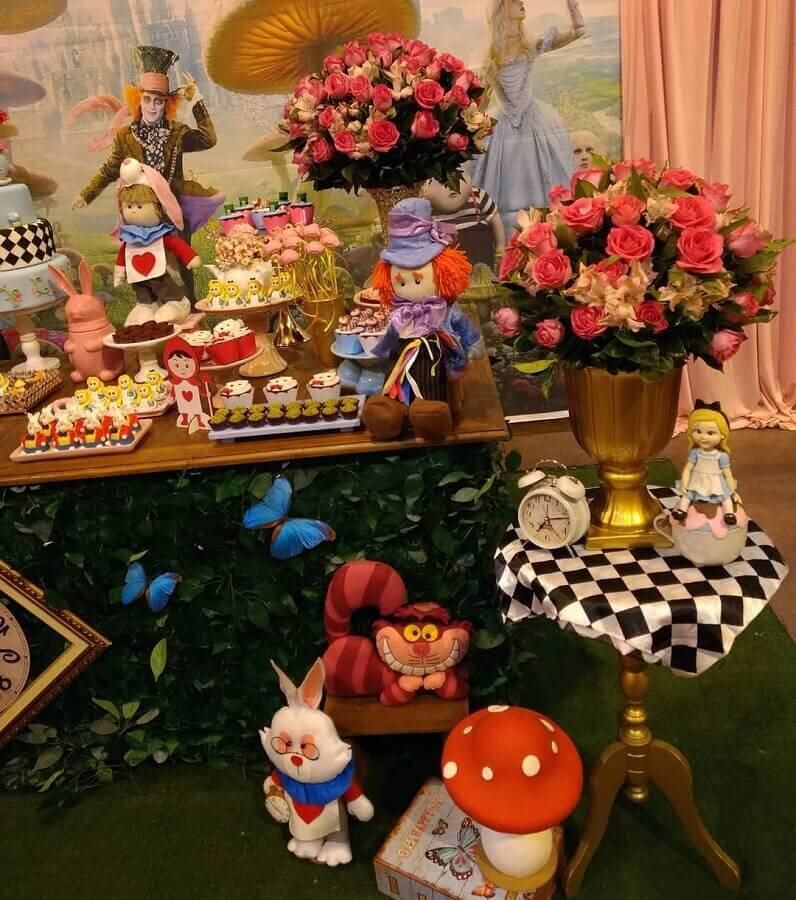 arrangement of roses and dolls of characters for decoration of alice party in wonderland Photo Alessandra Braga