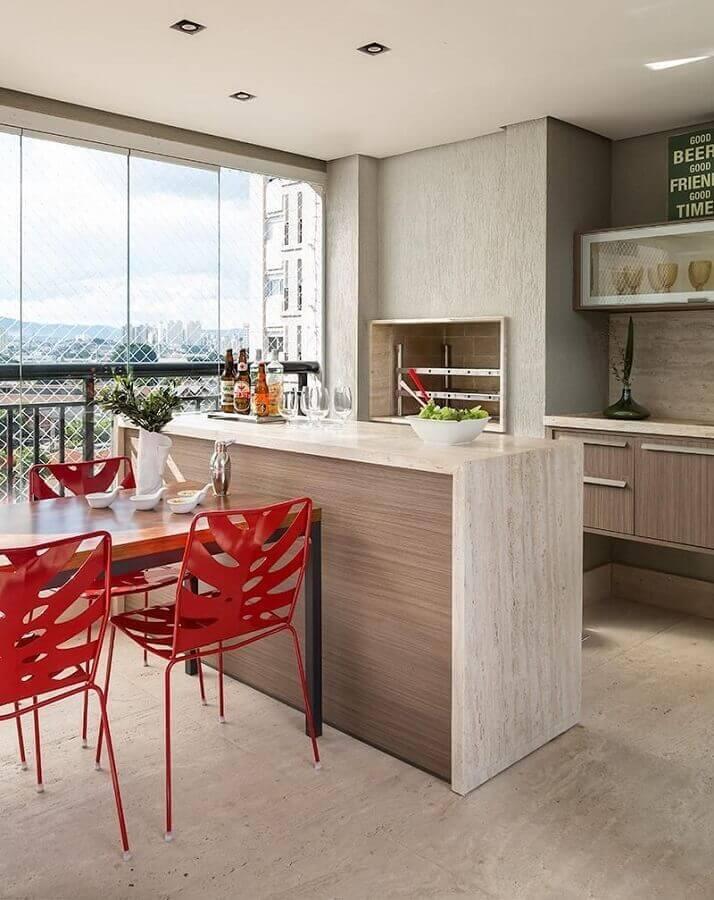 bancada para varanda gourmet decorada com churrasqueira e cadeiras vermelhas Foto Eliane Mesquita