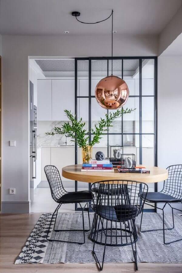 cadeiras pretas modernas para sala de jantar decorada com mesa de madeira redonda Foto Casa Vogue