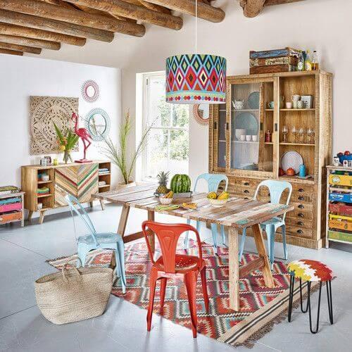 Cozinha com mesa de madeira com cadeiras coloridas
