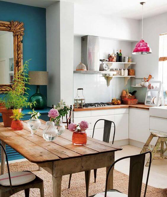Cozinha com mesa de madeira rústica com centro de mesa
