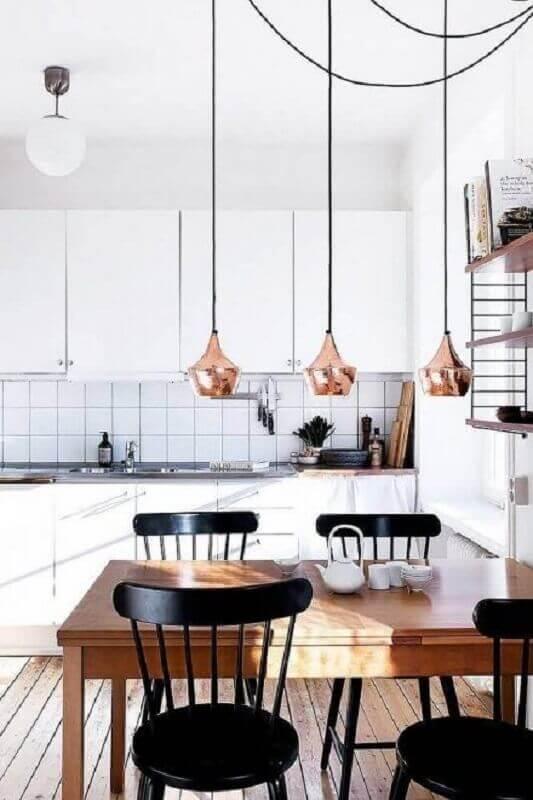 cozinha toda branca decorada com mesa com cadeira preta de madeira Foto Revista VD