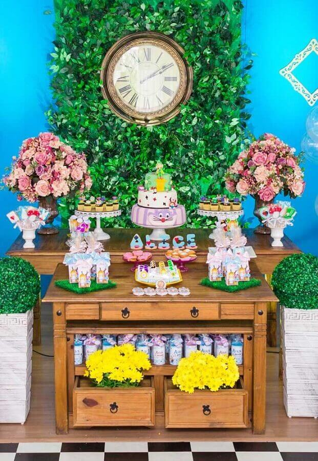 Alice in Wonderland simple party decoration with wooden table and foliage panel Photo Pinterest