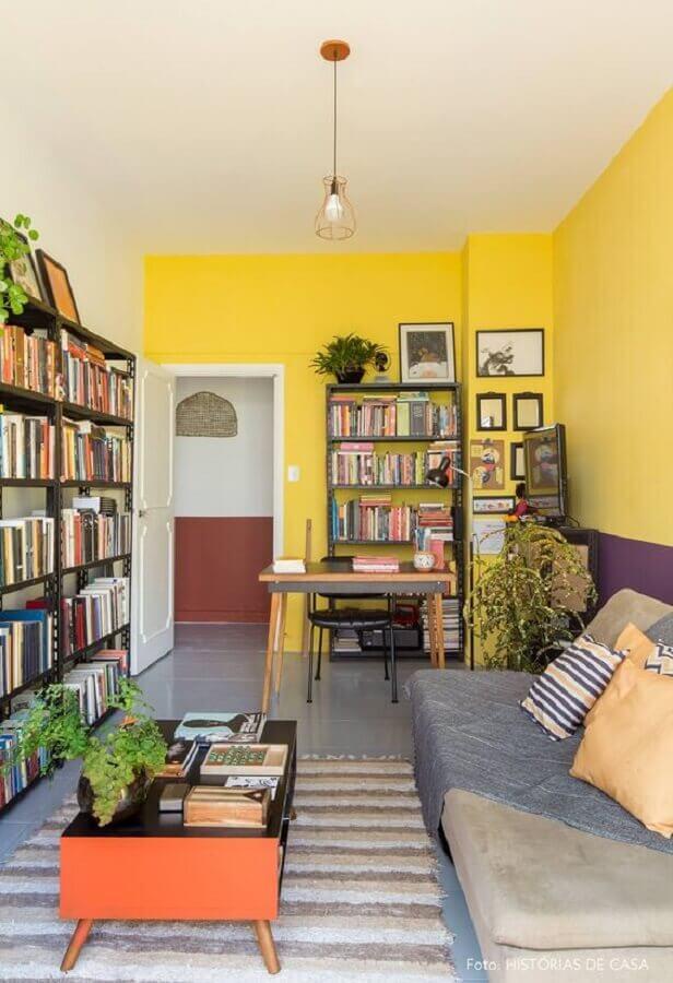 decoração de sala amarela com estante de livros e tapete listrado Foto Histórias de Casa