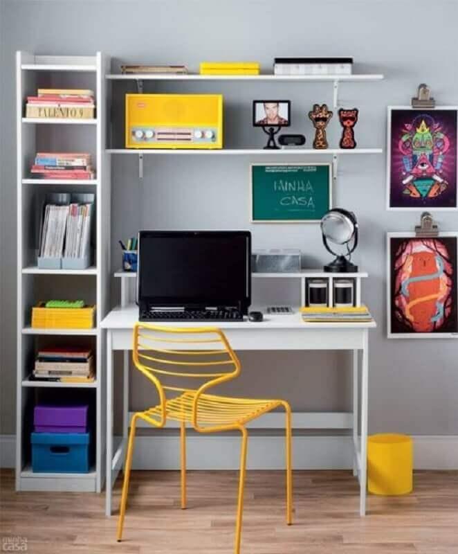 decoração simples com cadeira amarela e escrivaninha branca com estante Foto diCasa