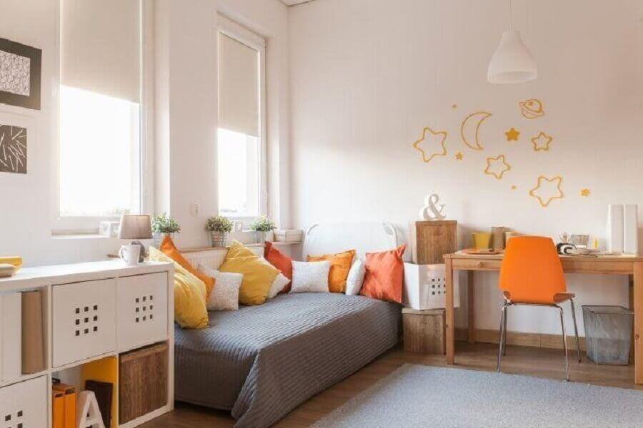 decoração simples para quarto de menina com branco e cinza com almofadas amarelas e laranjas Foto Istock