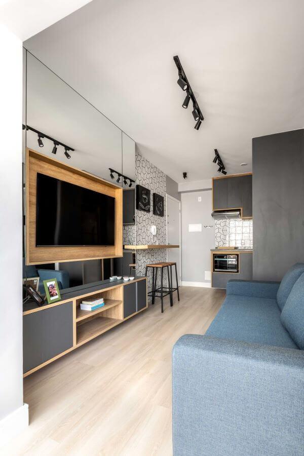 Sala de estar com painel para tv espelhado e de madeira