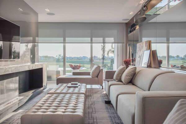Sala de estar com parede espelhada e sofá bege