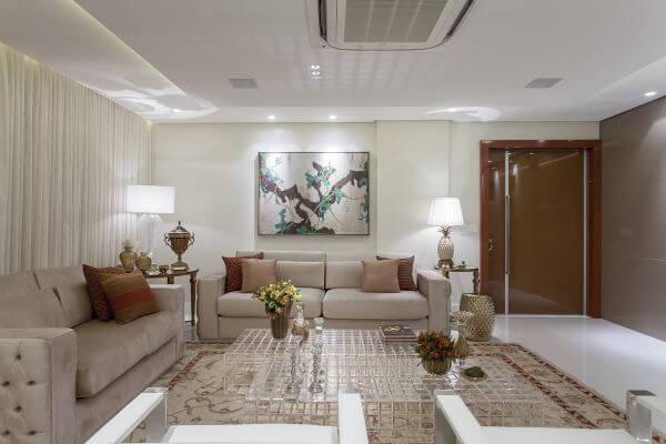 Sala de estar com sofá bege e mesa de centro transparente