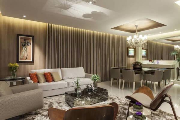 Decoração de sala de estar com sofá bege e poltrona marrom
