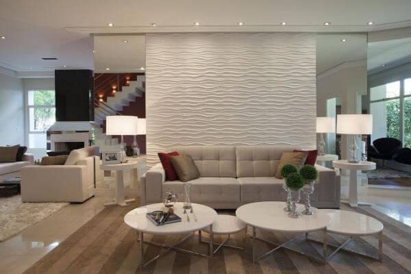 Sala de estar com sofá bege e parede espelhada