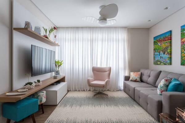 Sala de estar com painel para tv e puff colorido