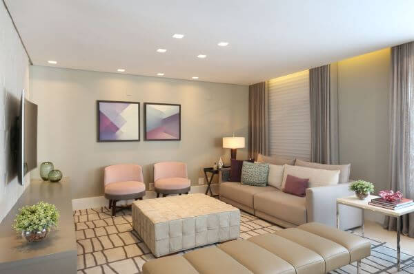 Sala de estar com poltronas cor de rosa e sofá bege