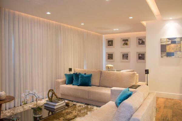 Decoração de sala de estar com sofá bege e almofadas azul em destaque