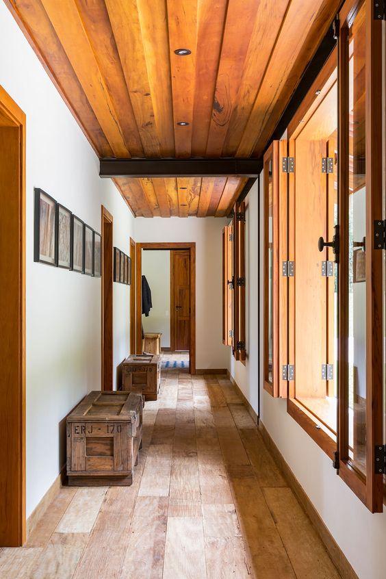 Janelas de madeira no corredor para iluminar a casa