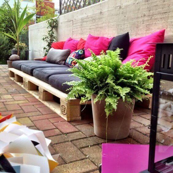 Jardim com sofá de palete preto e rosa