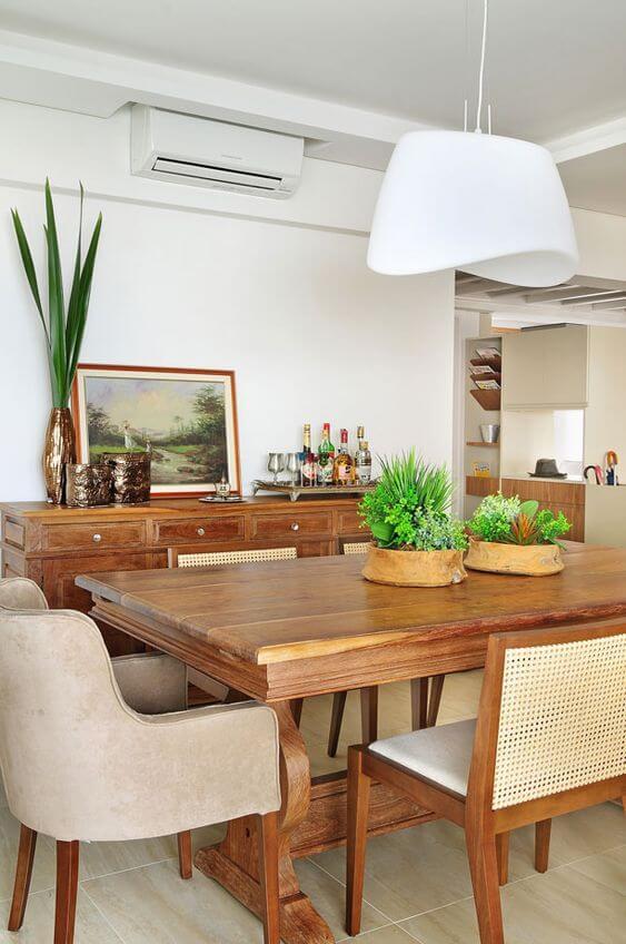 Mesa de jantar madeira rústica com lustre branco e plantas na decoração