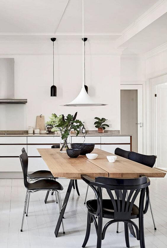 Mesa de madeira com cadeiras e lustres estilo industriais