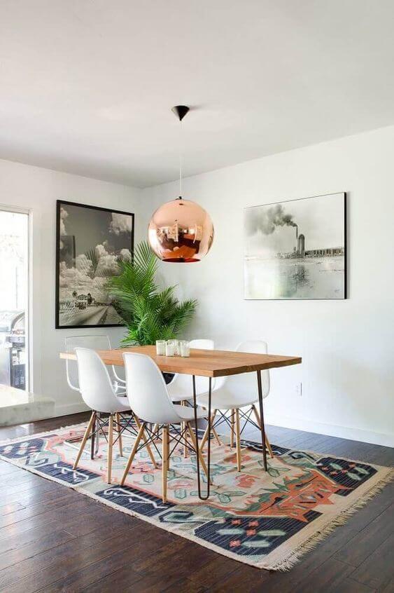 Mesa de madeira rústica com cadeira branca e lustre rosé