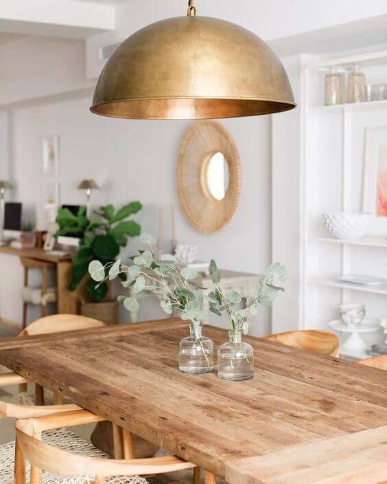 Lustre dourado com mesa de madeira rústica