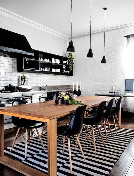 Mesa de madeira rústica na cozinha com cadeiras pretas