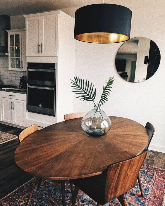 Mesa de madeira rustica na sala de jantar com lustre preto