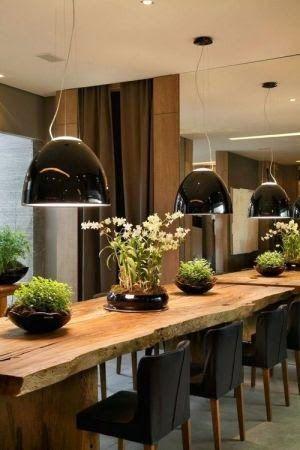 Mesa de madeira rústica na sala de jantar com lustre preto