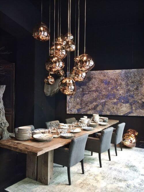 Lustre dourado acima da mesa de madeira rustica