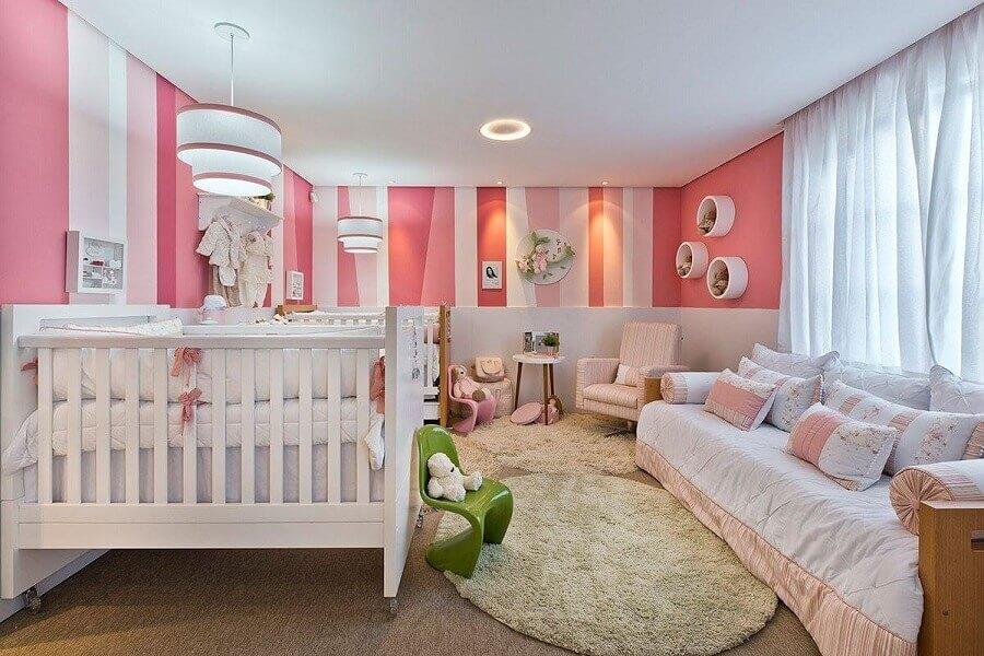 quarto de bebê rosa e branco decorado com papel de parede listrado e nichos redondos Foto Webcomunica