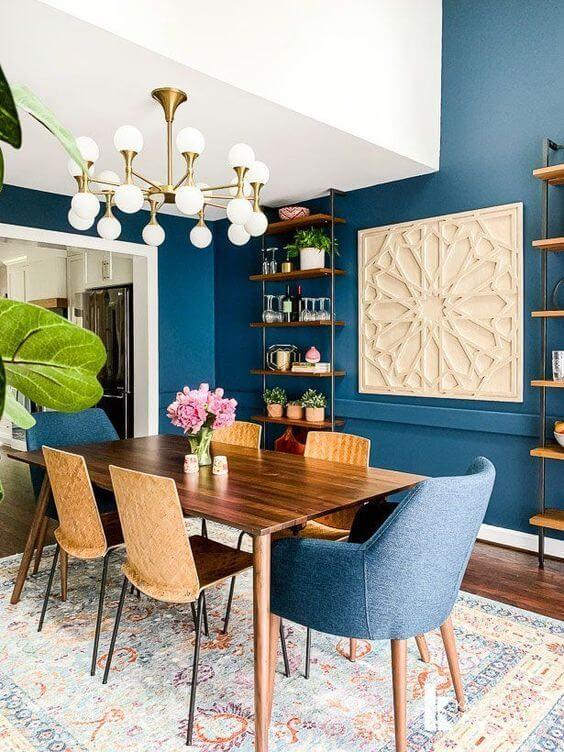 Sala azul com mesa de madeira rústica e lustre dourado