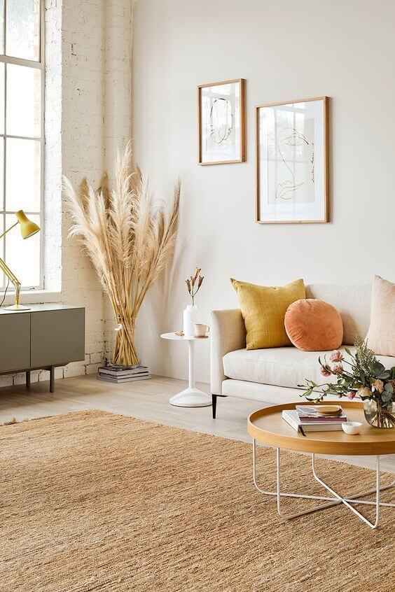 Sala com sofá bege e almofadas em tons quentes