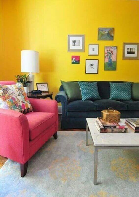 sala com parede amarela decorada com poltrona rosa Foto Pinterest