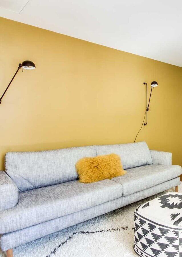 sala com parede amarela decorada com sofá cinza moderno e arandela articulável Foto Dcore Você